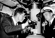 President John Kennedy looks through the periscope of the nuclear submarine USS Thomas A. Edison. At right is his Naval Aide, Capt. Tazewell Shepard. ...