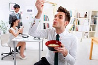 Businessman eating noodles