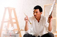 A male artist painting in studio
