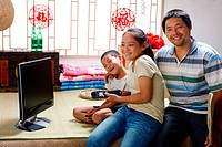 Boy and girl looking at computer display display with their father
