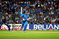 Indian batsman M S Dhoni plays his shot while Sri Lankan captain, wicketkeeper Kumar Sangakkara looks on during the ICC Cricket World Cup final betwee...