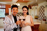Young couple holding glasses of red wine in kitchen