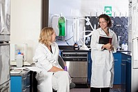 Two laboratory scientists talking to each other in a laboratory