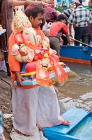 Man carrying idol of Lord Ganesh Pune Maharashtra India Asia Sept 2011