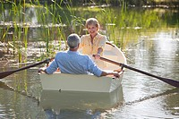 Senior couple on rowboat on sunny lake