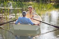 Senior couple on rowboat on sunny lake