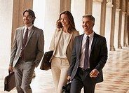 Smiling business people walking along corridor