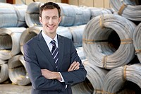 Portrait of smiling businessman in front of coiled cable in warehouse
