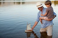 Grandfather and grandson wading in lake with toy sailboat