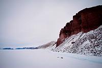 Red cliffs in snowy landscape