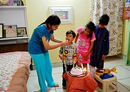 Elder sister giving piece of cake to little younger brother on his birthday MR704