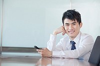 Chinese businessman holding cell phone in conference room