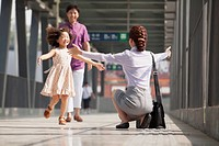 Chinese businesswoman greeting daughter on train platform
