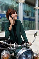 Chinese business woman on cell phone on motorcycle
