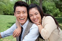 Smiling Chinese couple hugging in park