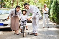 Chinese parents pushing son on bicycle