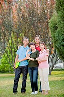 Chinese family holding plastic disc in park