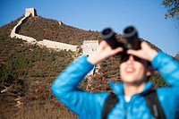 Chinese woman using binoculars by Great Wall
