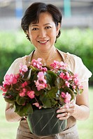 Older Asian woman holding potted plant in garden