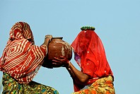 Rajasthani ladies helping other to carry earthen pot ; Rajasthan ; India