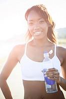 Mixed race woman drinking water bottle