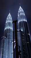 Petronas towers Kuala Lumpur at night with construction crane on the foreground