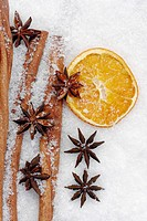 fruits of star anise - Illicium verum - cinnamon sticks - Cinnamomum cassia - dried orange slices - potpourri on artificial snowflakes