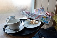 Woman reading newspaper at cafe window with empty cup and plate, England, UK
