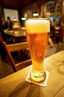 Glass of wheat beer on a table in an old restaurant , Stuttgart , Germany