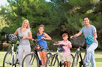 Portrait of smiling family with bikes