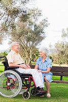 Woman chatting to partner in wheelchair in the park