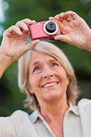 Older blonde woman taking a photo