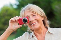 Smiling older woman taking a photo