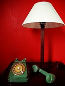 Green vintage telephone on a red background