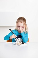 Young girl eating a plate of sushis and makis with chopsticks