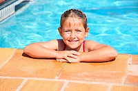 Happy girl smiling at swimming pool