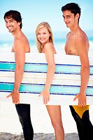 Profile of three surfers standing on a beach together and holding a surfboard