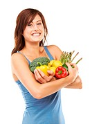 Studio shot of a young woman holding a variety of vegetables and fruit in her arms isolated on white