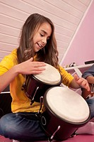 Girl playing drums, smiling