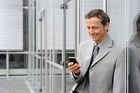 Europe, Germany, Bavaria, Businessman using mobile, smiling