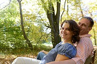 Germany, Bavaria, Couple sitting on bench, smiling