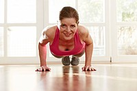 Germany, Duesseldorf, Mature woman doing push ups at home