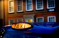 taxi in front of a classic office building in the City of London, England, UK
