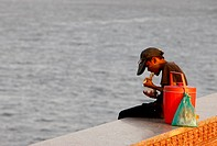 Young boy eating in front of Mekong River. Phnon Penh, Cambodia.