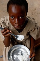 African girl eating rice, Togo.