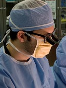 Plastic surgery resident wearing medical loupes, magnifying devices worn on frames on the face to provide a closer view of the surgical field.