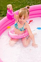 little blond girl plays in plastic pool