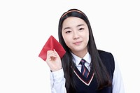 a female student wearing school uniform ready to throw a paper airplane