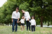 Family running hand in hand on grass