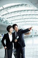 a businessman and woman looking at something together in Incheon airport